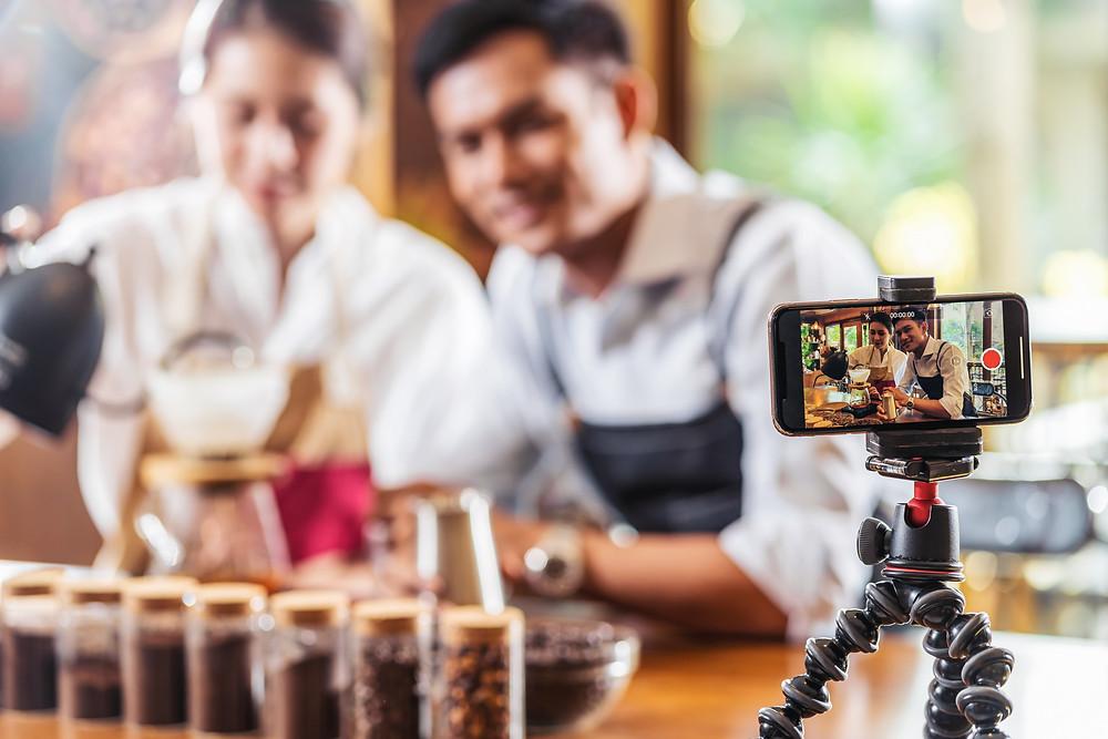 Na foto, um casal sendo filmado por um celular preso a um tripé. Esta foto tem o objetivo de ilustrar pessoas que ministram cursos online.