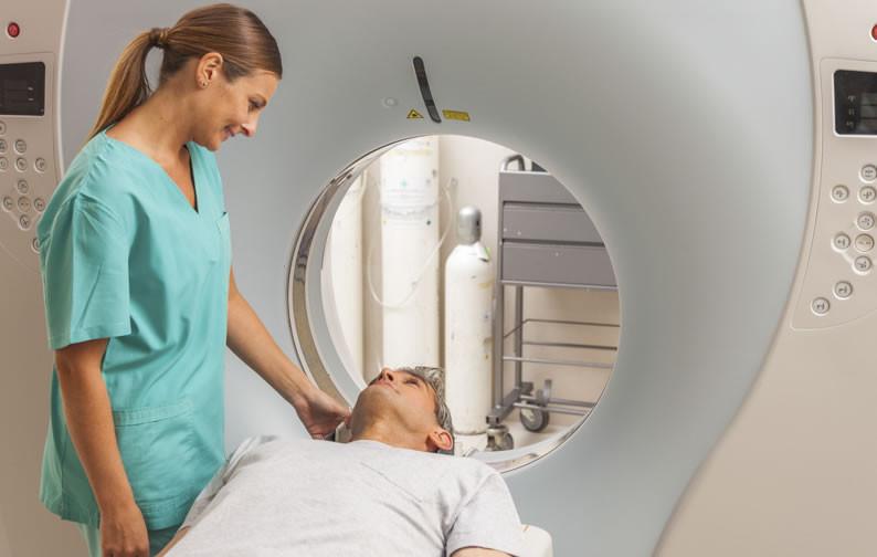 Foto de um homem fazendo um exame de ressonância magnética em um laboratório médico junto de uma médica.