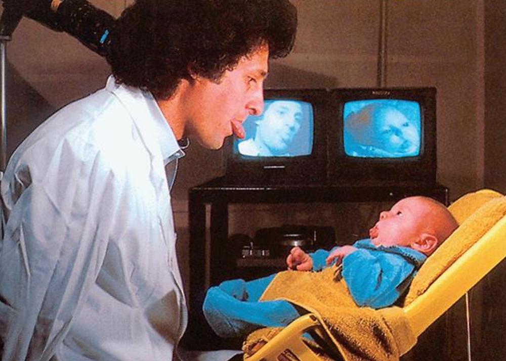 foto de um homem adulto mostrando a língua para uma criança e a criança mostrando a língua para o homem repetindo o processo comportamental de espelhamento.