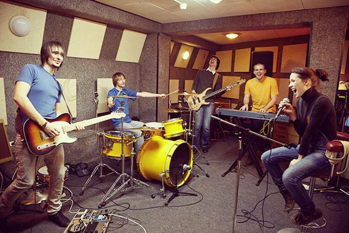 foto de uma banda ensaiando num estúdio. A foto tem o objetivo de ilustrar a conexão das pessoas.