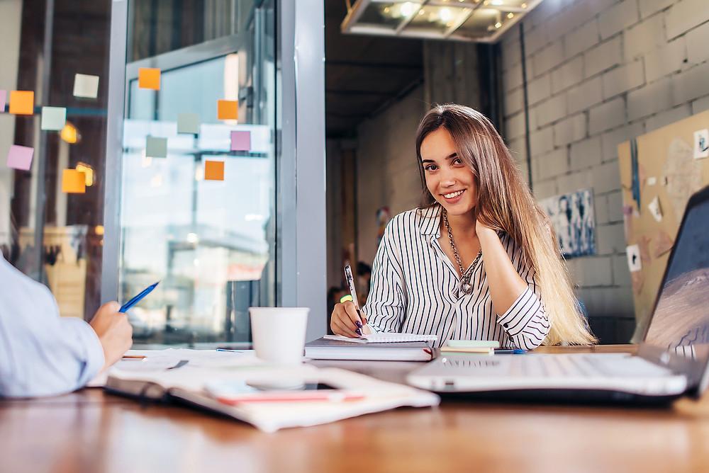 Foto de uma mulher sorridente sentada na mesa de um escritório escrevendo.