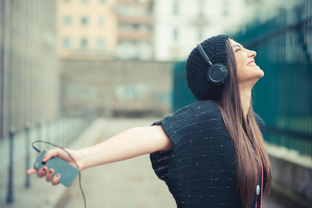 foto de uma mulher sorridente ouvindo música com fones de ouvido. A foto expressa liberdade.