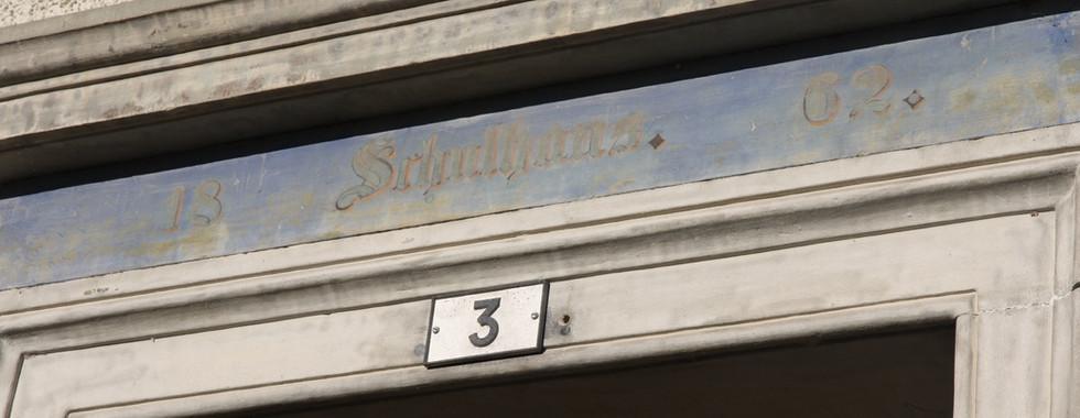 Inschrift über dem alten Schulhaus, das 1826 gebaut wurde. Heute ist es ein Wohnhaus.