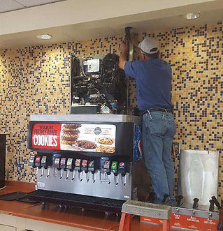 Troy from Advantage working on a soda machine in Stillwater.