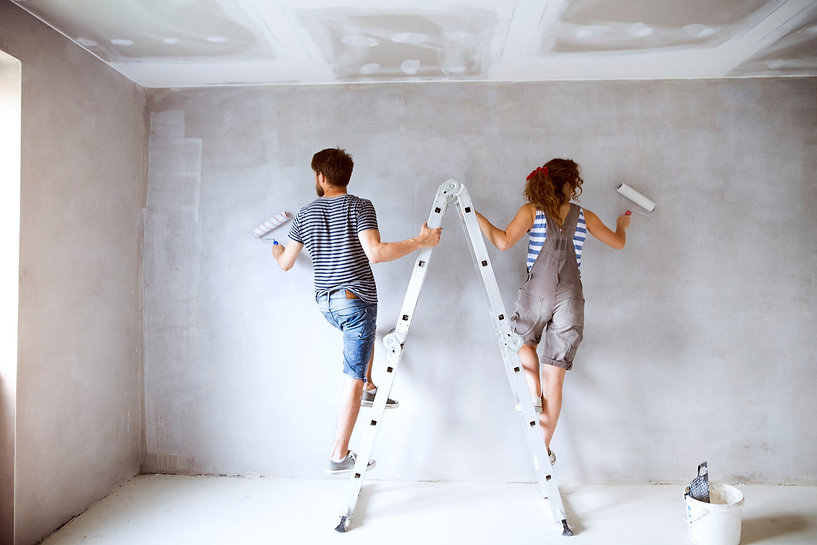 Young couple painting walls in their new