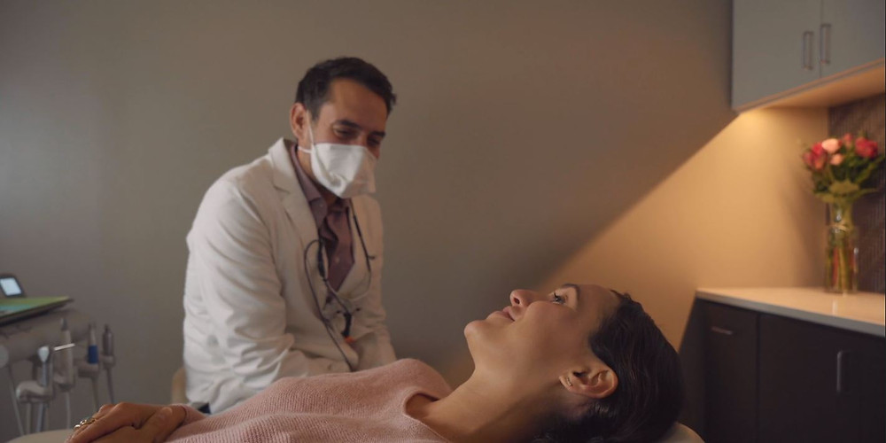 Dr. Bethell describes the process of a smile makeover to a patient at Blue Door.