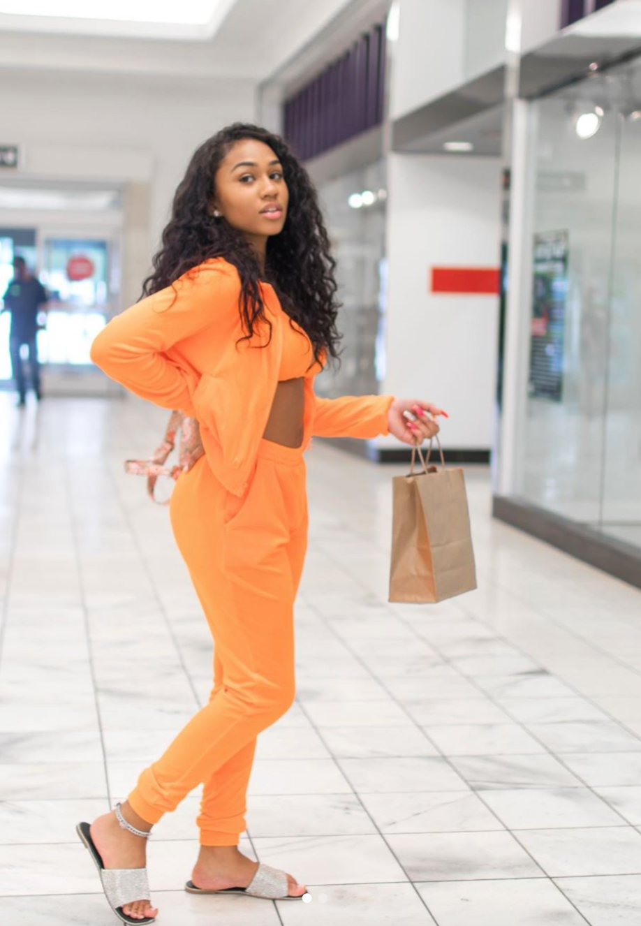Girl standing while wearing a bright orange sweatsuit
