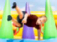 Child jumping on colorful playground tra