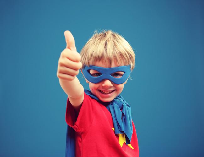 A young boy superhero giving you a thumb
