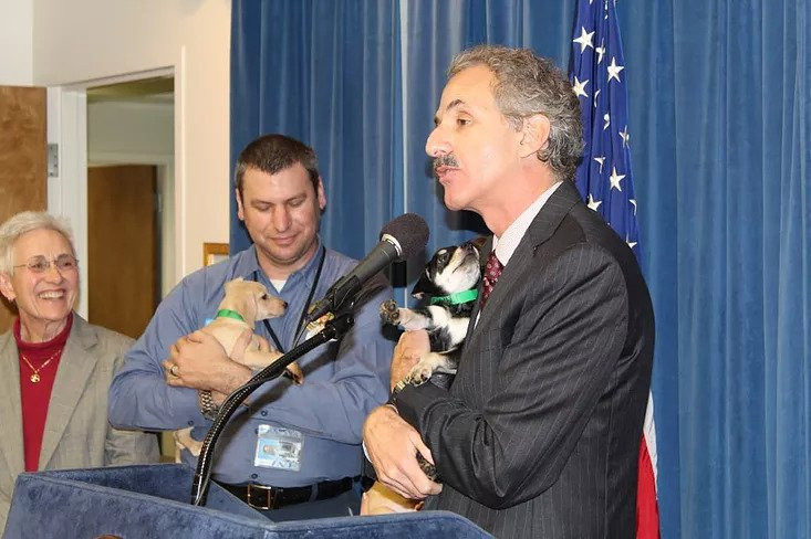 City Attorney Mike Feuer at puppy scams press conference holding 8 week old Comet.