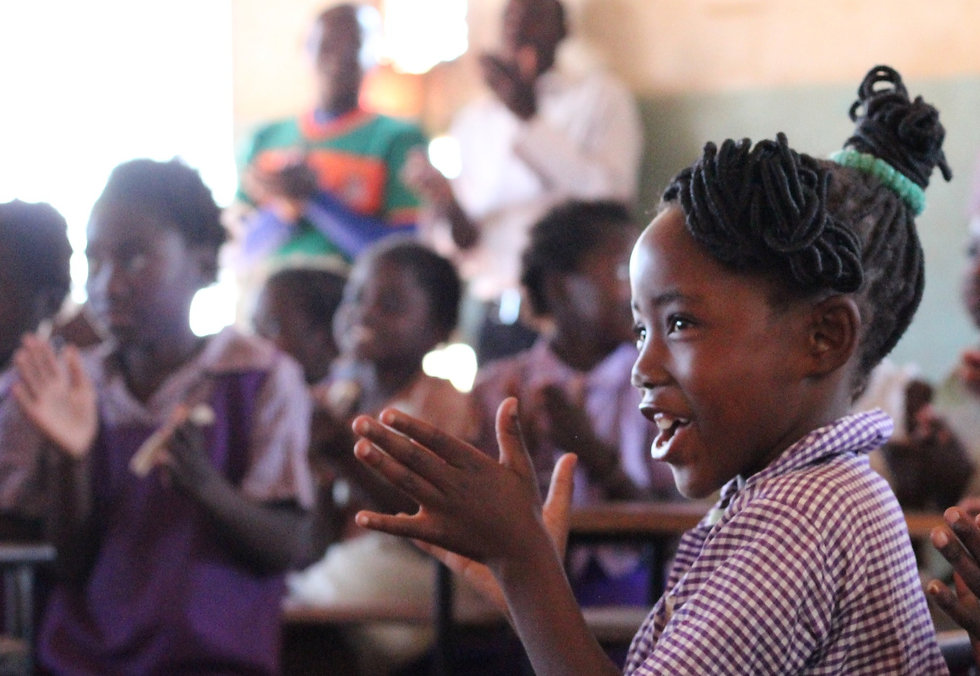 A young student clapping and singing a Maanu Mwambi School in Kitwe, Zambia