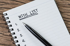 Wish list concept, pen on white paper note pad with handwritten headline as Wish List and