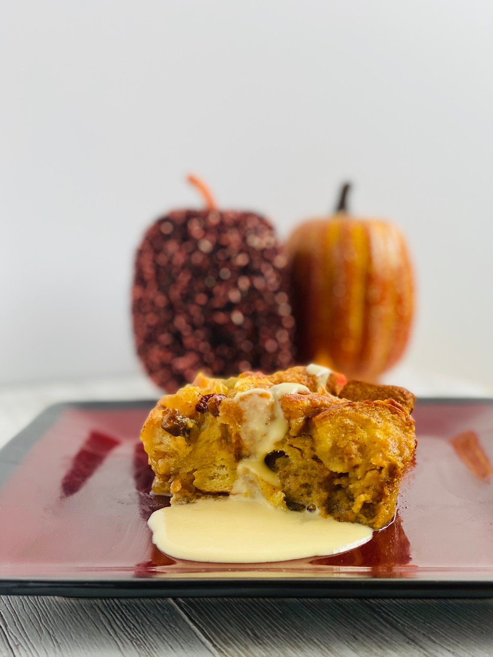 Close-Up Pumpkin Bread Pudding with Crème Anglaise on a red plate with sparky pumpkins in the background