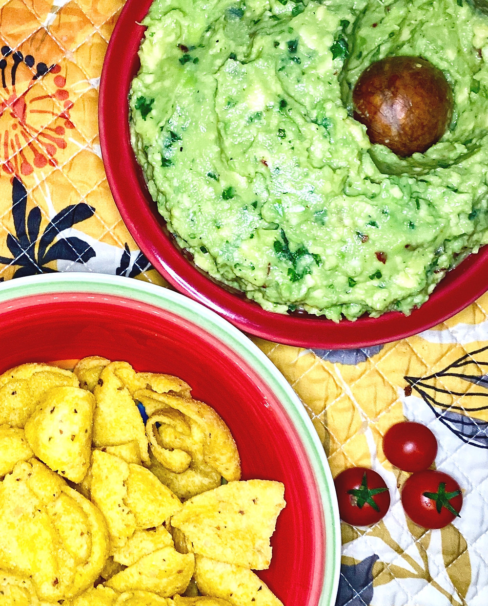 A bowl of Guacamole with it's pit and a bowl of Frito Lay's