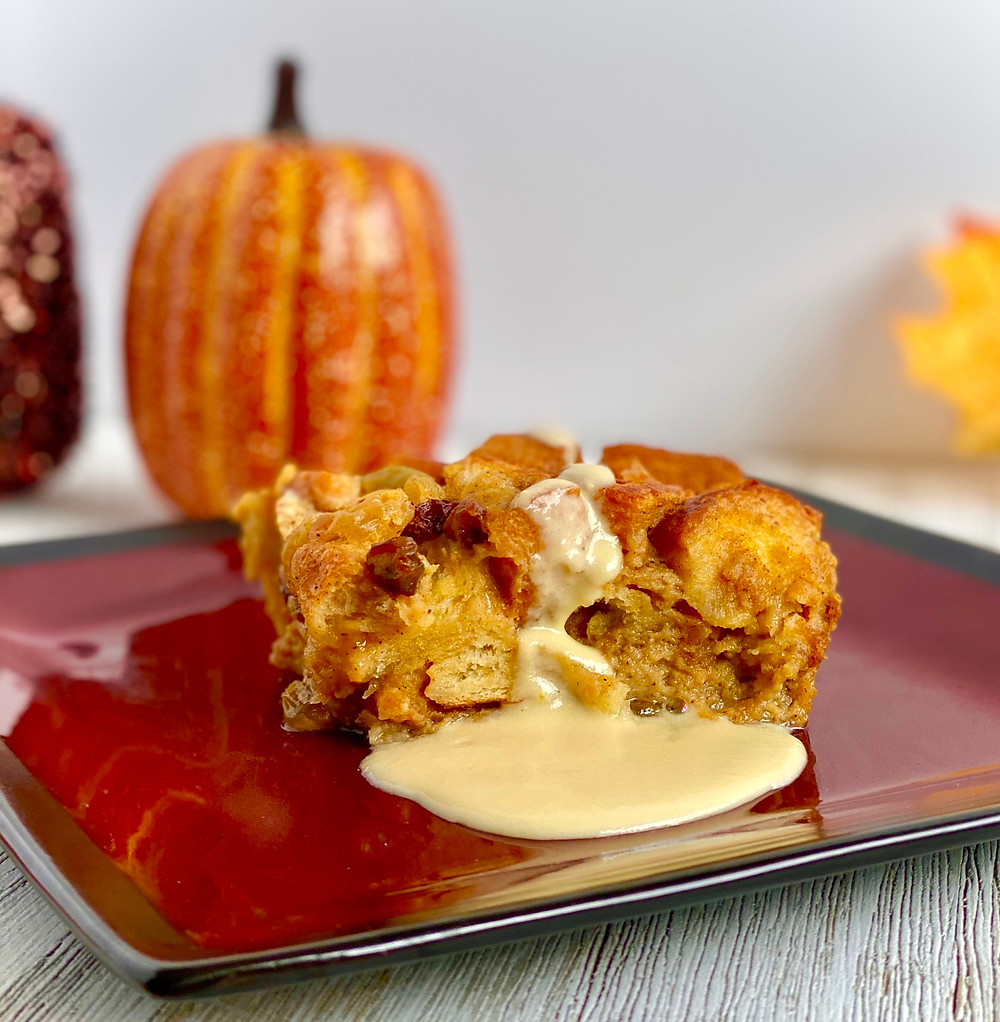 Pumpkin Bread Pudding with Crème Anglaise on a red plate with sparky pumpkins in the background and a leaf