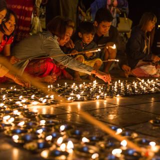 Lighting prayer candles at Kyaiktiyo