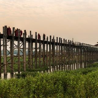 Monks crossing the U Bein Bridge at sunrise