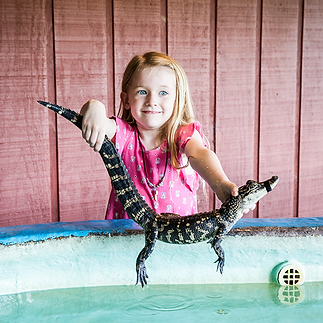 Charlotte holding alligator CROPPED.png