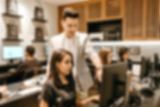 man-teaching-woman-in-front-of-monitor-3