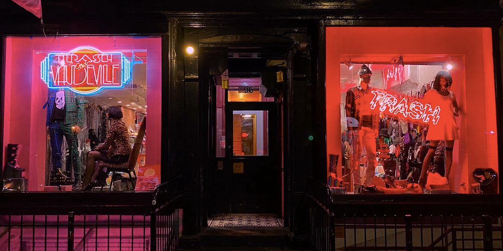 The exterior of the store Trash and Vaudeville in New York City. There are red and pink neon signs in the windows with mannequin wearing punk fashion.