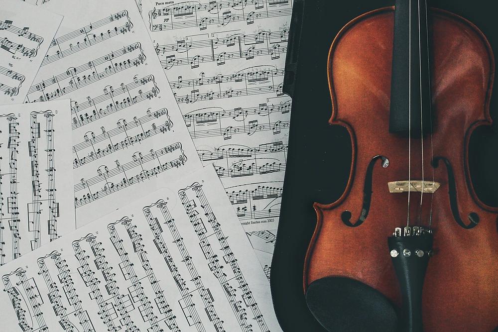 Sheet music next to a cello.