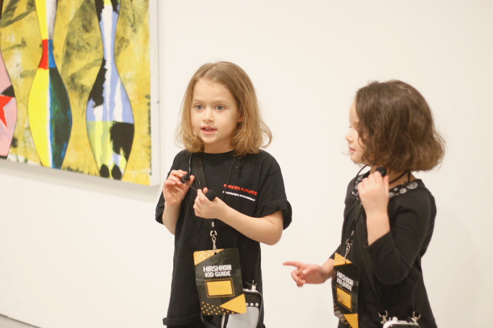 Two young girls carrying portable microphones stand  next to an artwork and talk about it to a group of  people. The group is out of the frame.