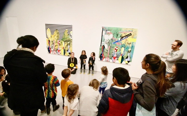 A large group of people observes two colorful  paintings from a safe distance while two young girls standing in front of the artworks talk to the group. Experience Developer Fabiola R. Delgado is sitting on the floor next to the girls.