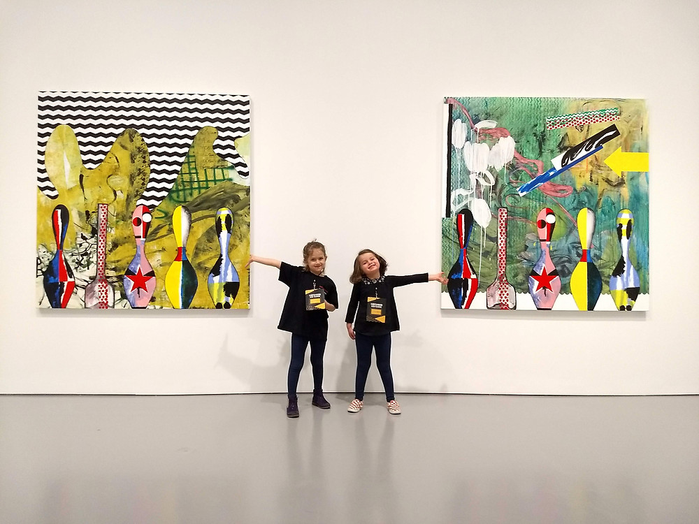 Two young girls stand in front of large colorful paintings by artist Charline von Heyl. They are smiling  and their arms are open, showcasing the artworks on either side.
