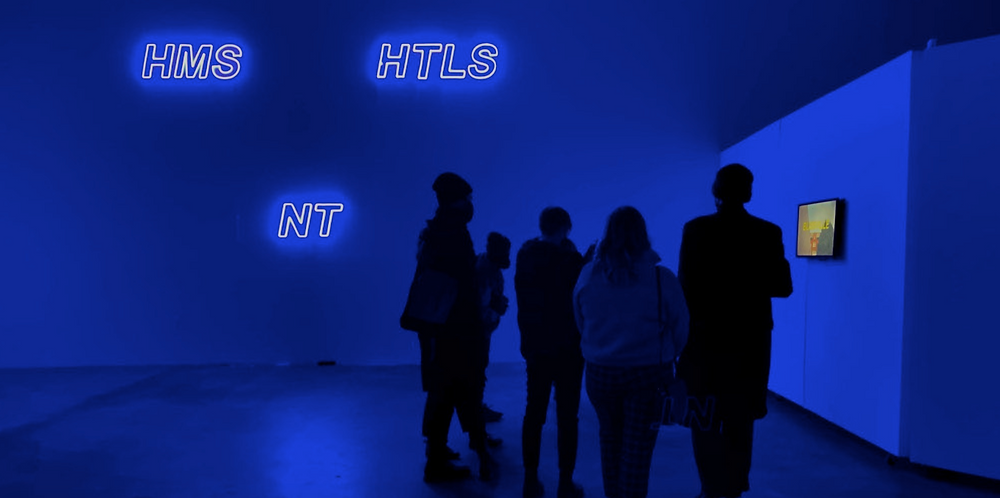Museum visitors standing inside an exhibition space with blue neon lights.
