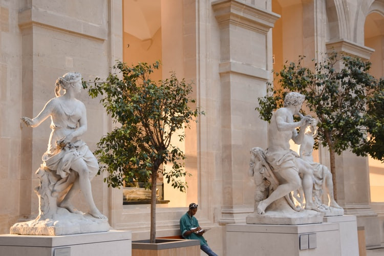 A person, surrounded by marble statues, sitting inside a museum listening to a museum audio guide with headphones on.