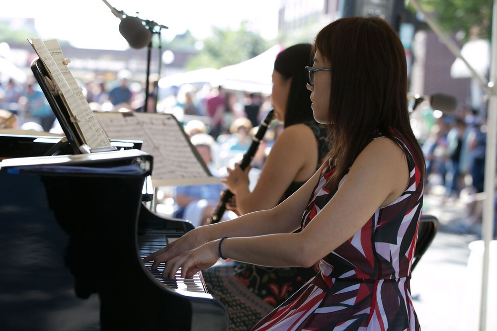 Musician playing a piano in front of a crowd during a previous Thirsty Ears Festival.