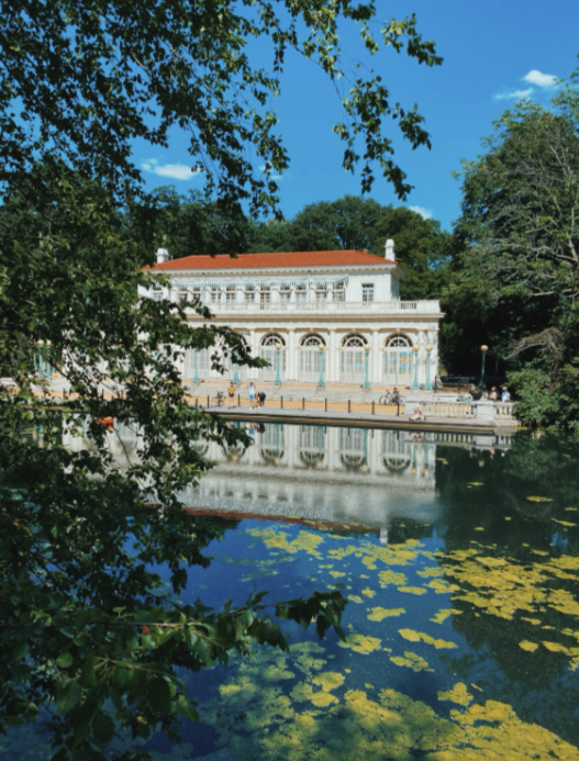 Exterior of the boathouse in Prospect Park Brooklyn. Surrounded by the green trees and pristine blue lake.