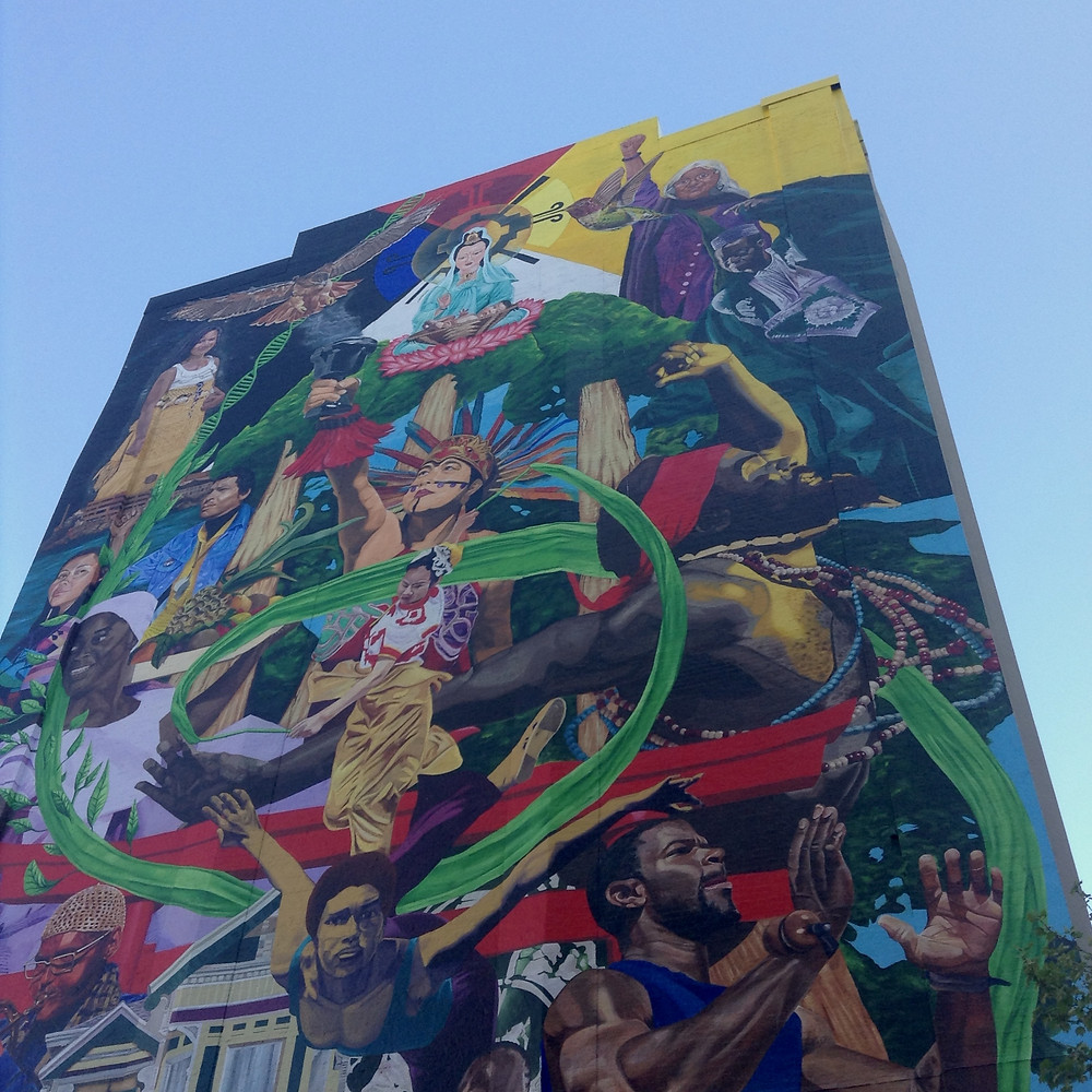 The colorful 360 mural, created by artist Desi Mundo and the Community Rejuvenation Project in 2020, located in Oakland, California. The mural includes paintings of artists, athletes, and activists with bright red and green colors surrounding them.