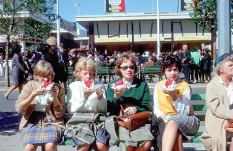 Archival image of fairgoers eating a belgian waffle with whipped cream and strawberries at the 1964–65 World's Fair in Queens, New York.