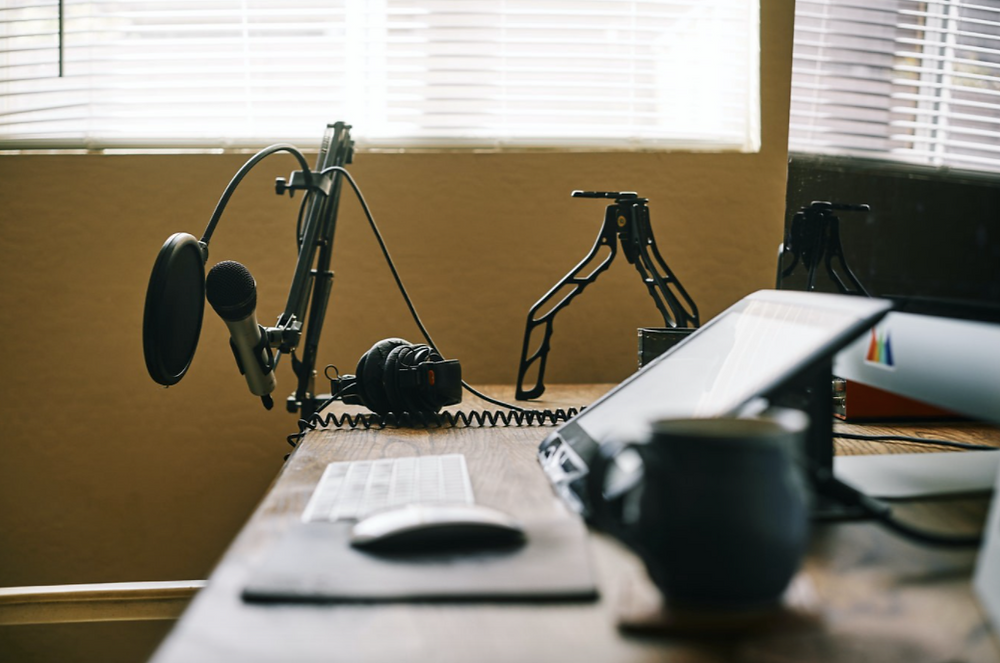Podcast recording studio with headphones, microphone, and a computer.