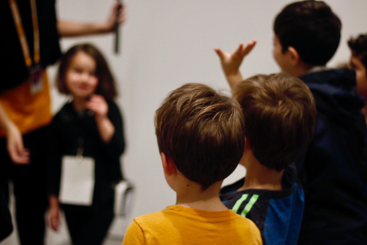 A young boy raises his hand to offer his comments, actively participating in a kid-led public tour.