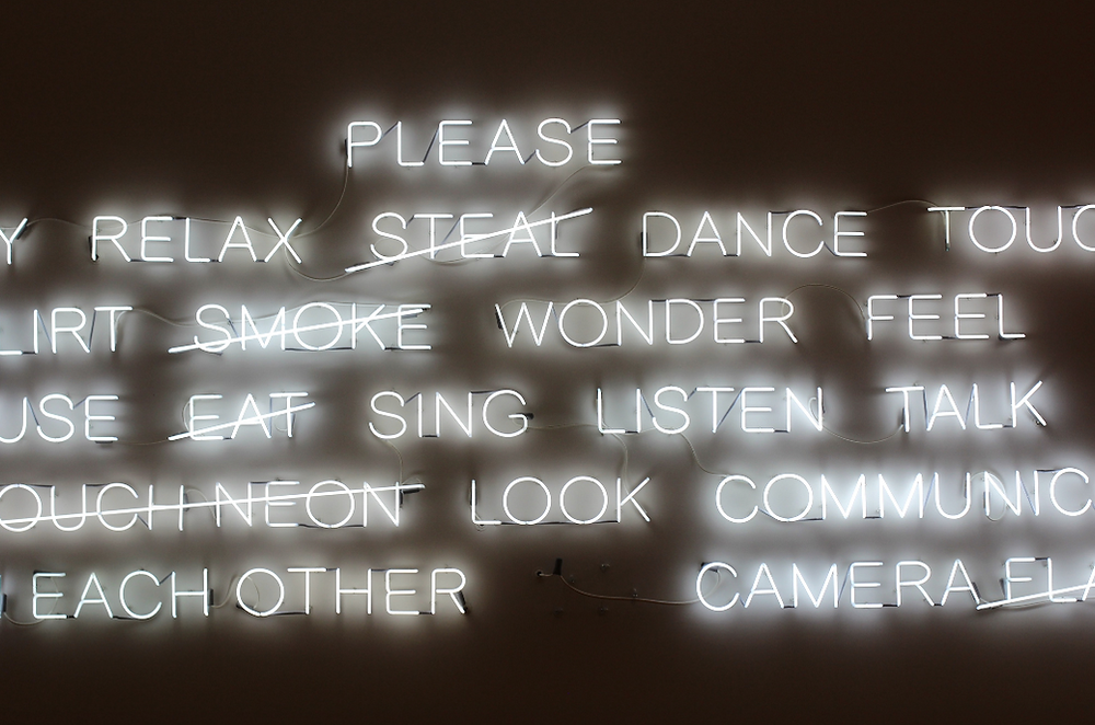 White neon words in a museum.