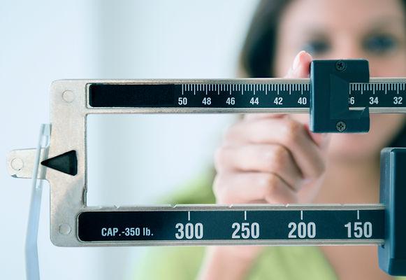 Donna su bilancia controlla i risultati della dieta