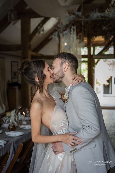 Bride and groom kissing in the barn