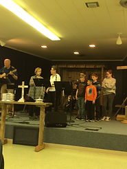 Our worship team leads worship while four of our youth do hand motions on stage.