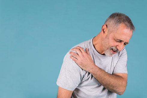 stressed-senior-man-with-shoulder-pain-on-blue-backdrop.jpg