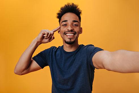 brown-eyed-man-in-blue-t-shirt-with-smile-makes-selfie-on-orange-wall.jpg