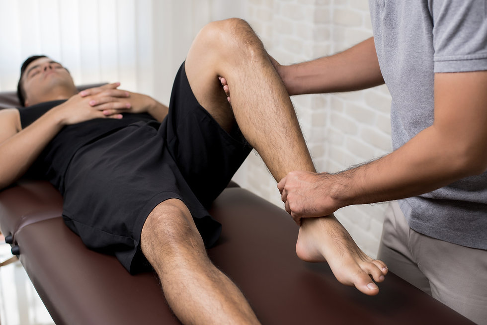 therapist-treating-injured-leg-of-athlete-male-patient-in-clinic.jpg
