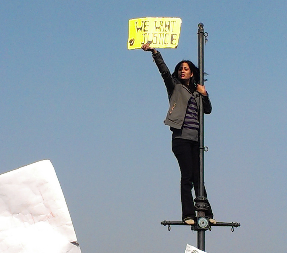 """A woman standing on a lamp pole with a sign saying """"we want justice"""""""