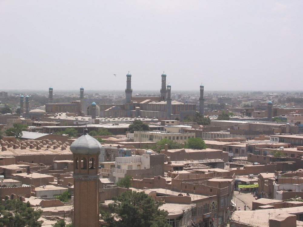 A picture looking over the rooftops of Herat, showng a minaret in the foreground and more in the background, with a few trees in between tan buildings