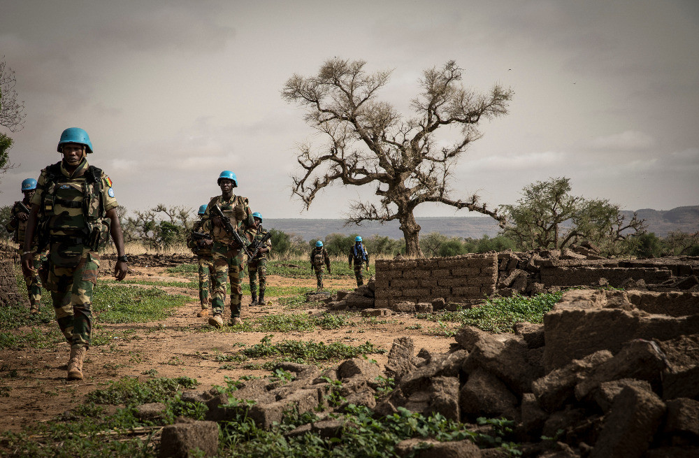 A photo of peacekeepers from Senegal walking past a tree and remains of a wall.
