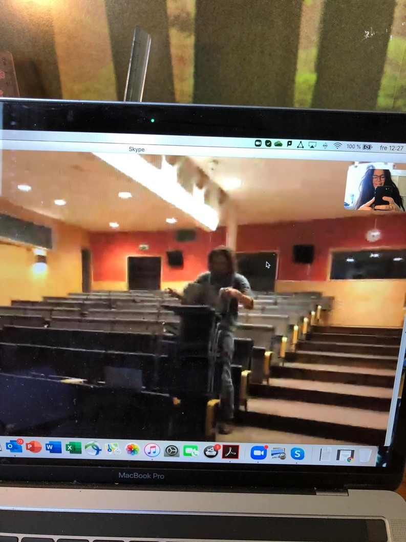 A photo of a video call on a screen, showing a man in an empty lecture hall.