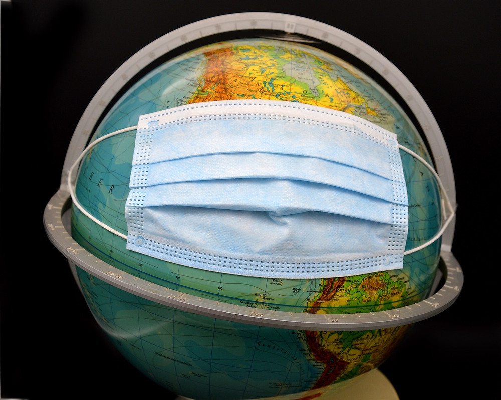 A picture of a surgical mask covering the USA on a globe