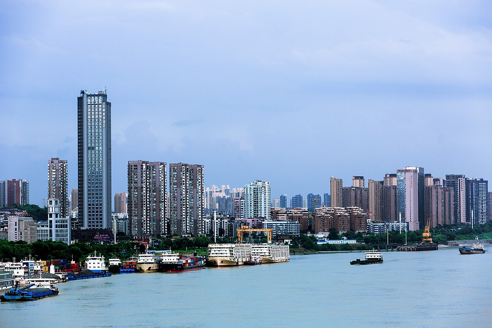 A photo of the riverside in Yichang, showing skyscrapers and industrial ships moared on the shore.