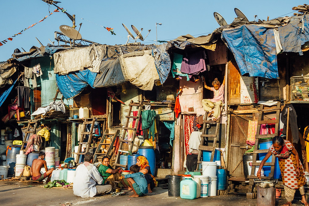 Picture of an urban poor neighbourhood in Mumbai, showing informal houses made from wood, tarps, and other materials, with satellite dishes on their roofs, along with some residents.